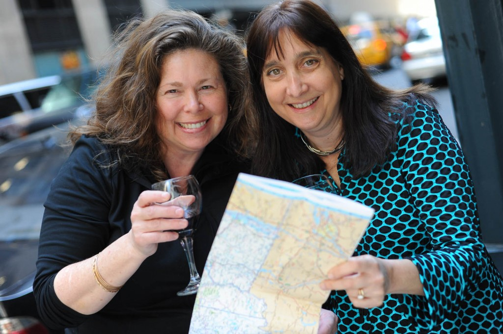 Getaway Mavens authors Sandra Foyt and Malerie Yolen-Cohn hold up a wine glass and road map.