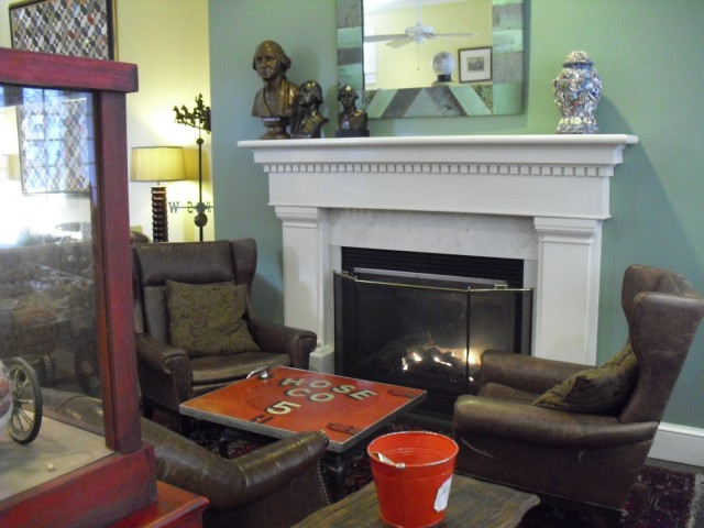 Fireplace – fire engine door coffee table – leather wingback chairs – lobby of hotel a former firehouse. | Cambridge MA