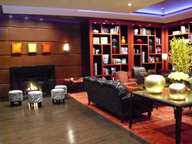 Chic colorful hotel lobby - red lacquer bookshelves - zebra striped stools