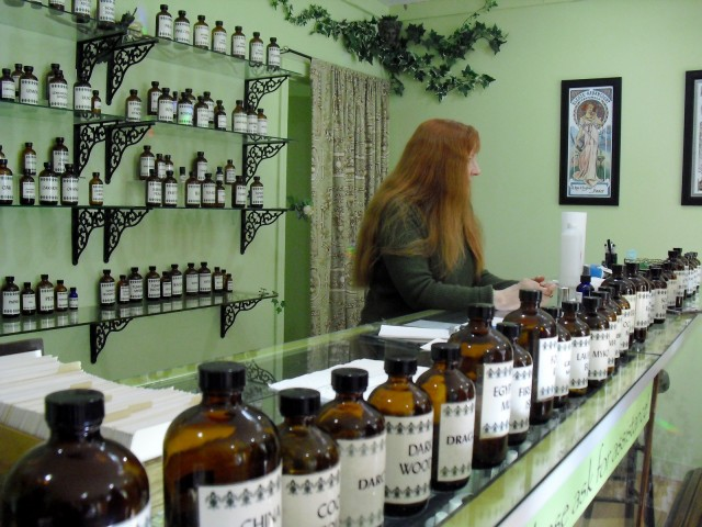 Owner of Aromasanctum Perfumes with array of apothecary jars filled with unusual oils and scents