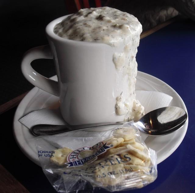 White mug overflowing with rich, chunky white New England Clam Chowder, The Sail Loft Restaurant, Boston, Massachusetts