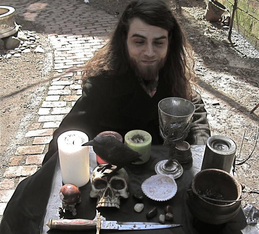 shot of male witch with candle, goblet, sword, bird, skull