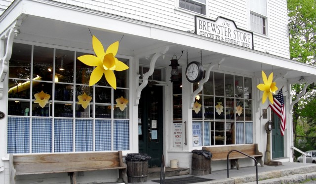 Large plastic lilies and inviting benches at entrance to a Cape Cod General Store