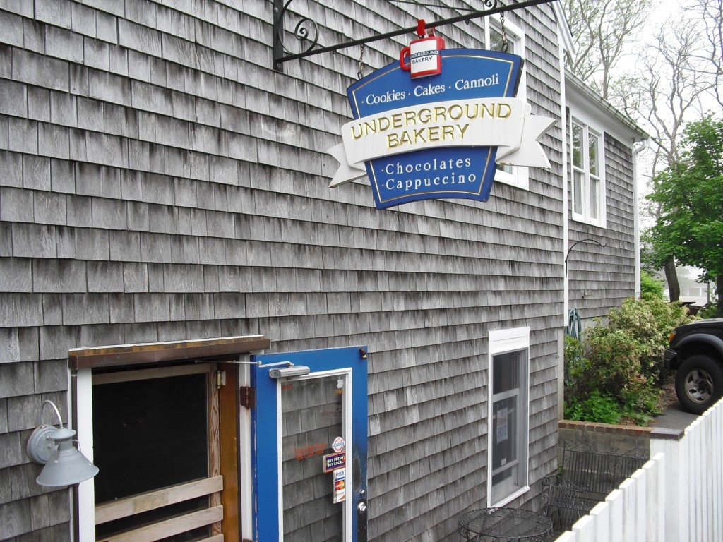 exterior shot of weathered grey clapboard building and bakery sign