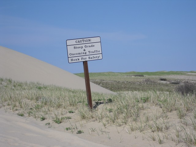 Caution sign warn of steep grade and oncoming traffic on sand dunes