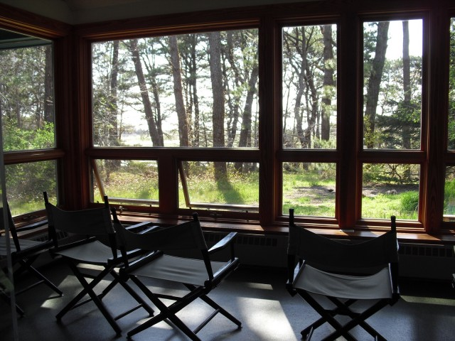slingback chairs face panoramic forest and salt marsh views