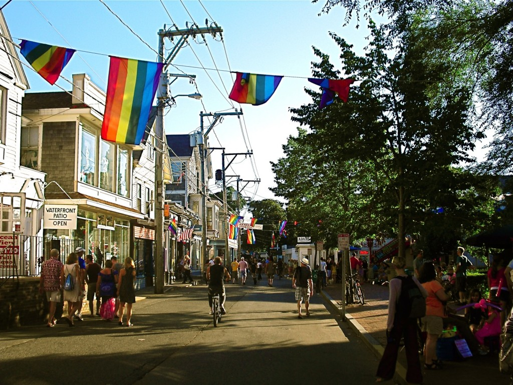 Rainbow flags flutter over shop lined street with many pedestrians