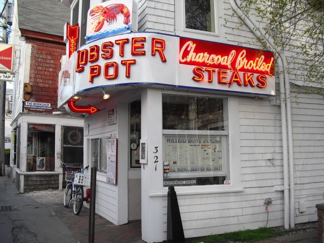 Exterior shot of restaurant with red neon signs of lobsters menu items. Lobster Pot Restaurant, Provincetown MA