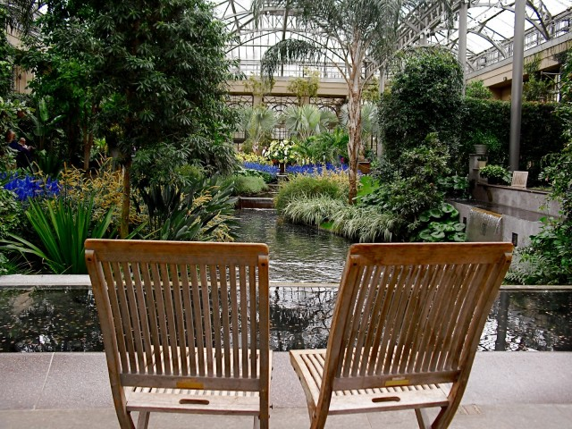 Teak chairs face landscaped pond within glass conservatory building. Conservatory, Longwood Gardens, PA #visitphilly #PATravelHappy @GetawayMavens