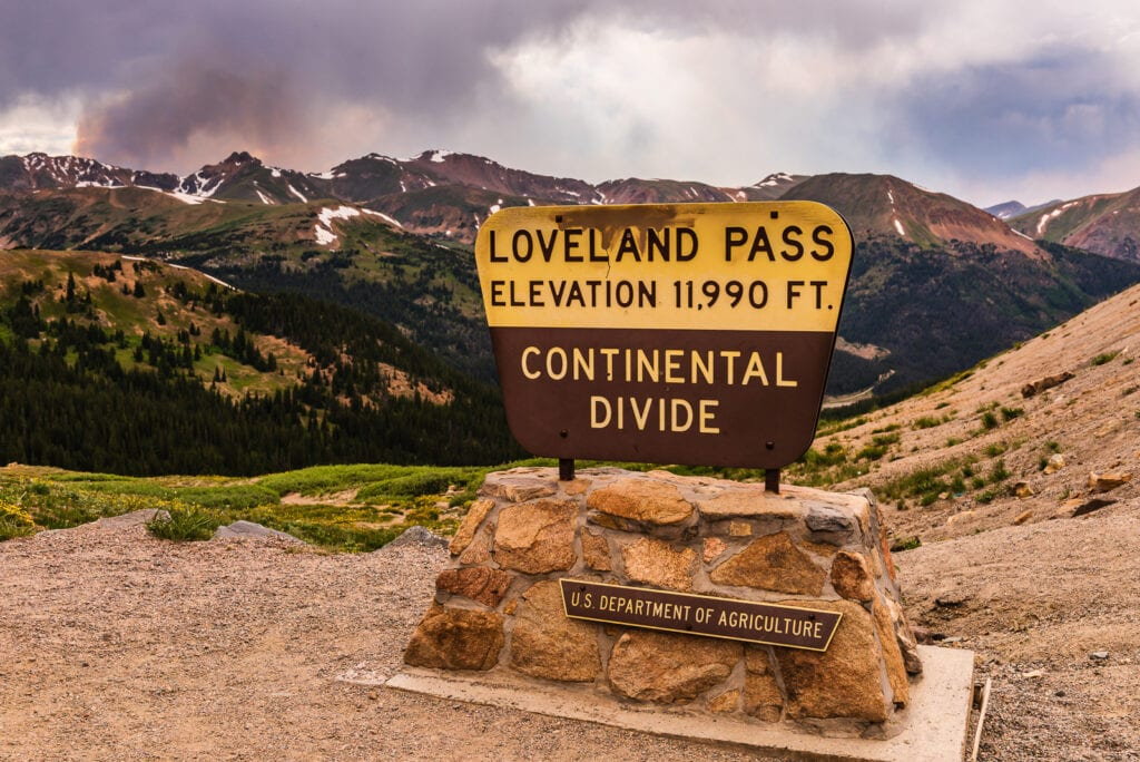 Sign at Loveland Pass on the Continental Divide with Rocky Mountains in the background.