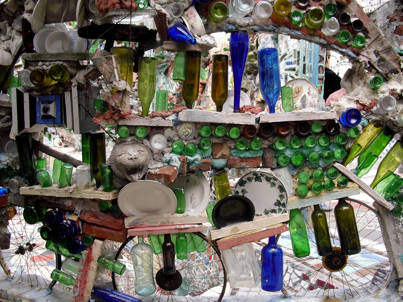 Colorful Pieces Of Plates, Bottles And Glass Objects Form A 3 D Mural In