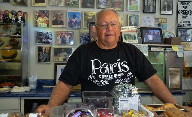 Mike Smith, owner of Paris Coffee Shop, posing with collection of memorabilia displayed on wall and on shelves.