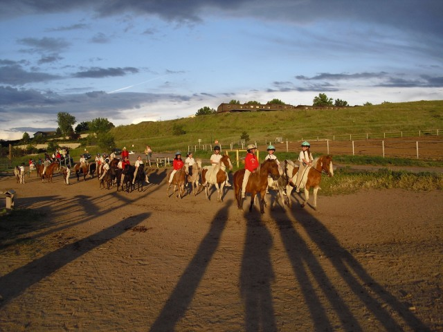 Young horse riders in setting sun at the foothill of the Rocky Mountains