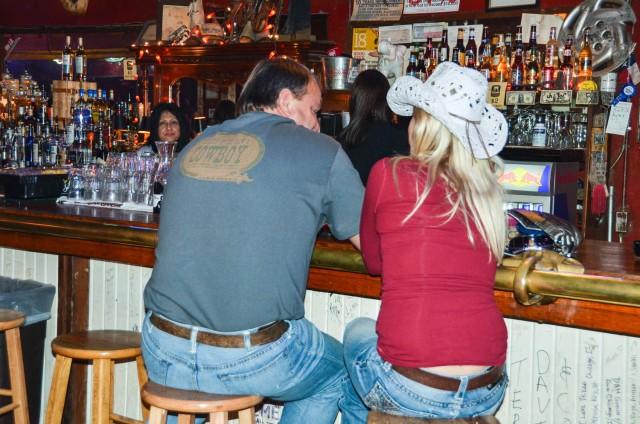 Couple sits on bar stools at White Elephant Saloon.