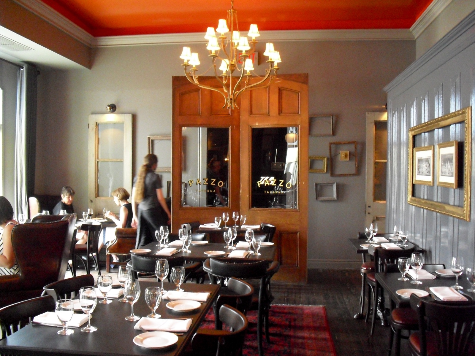 Interior Of Upscale Restaurant With Candle Lamp Chandelier And Mirror Armoire