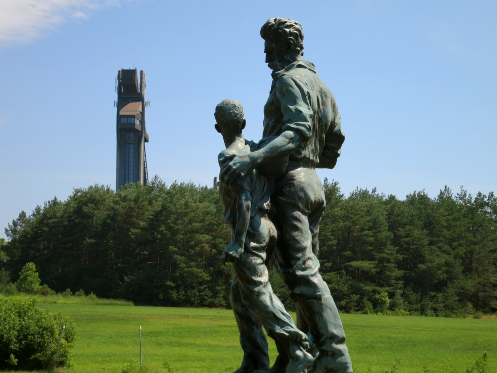 Statue of John Brown with child in shadow of Olympic Ski Jumps, Lake Placid, NY