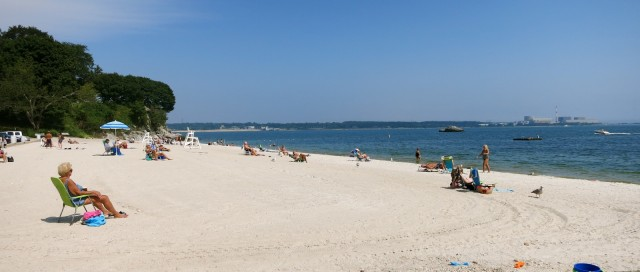 Beachgoers enjoy Niantic CT beach on cloudless day with nuclear power plant in background