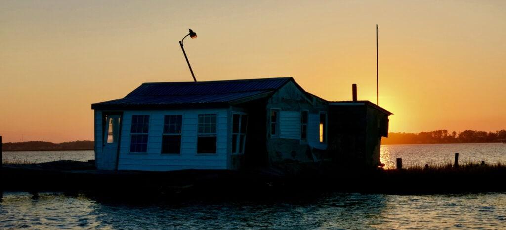 Sun sets behind floating house Captain Dans Boat Tour Chincoteague VA