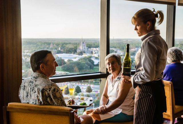 Waitress with wine bottle, couple dining with view of the Magic Kingdom. | California Grill | Disney World