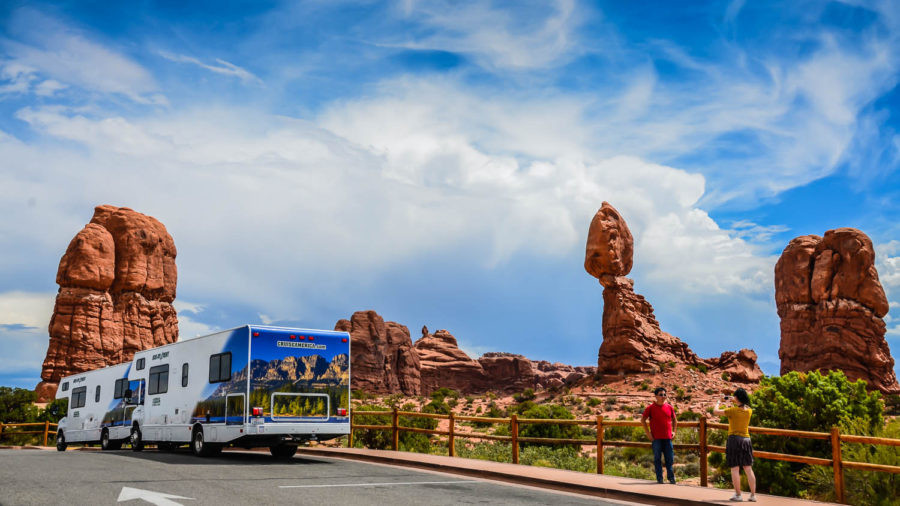 Tourists taking photos and a Cruise America RV in front of Arches National Park.