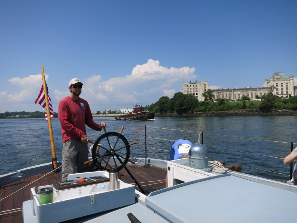 """Gundalow Captain sailing past the crumbling but still grand decommissioned Naval prison referenced in the movie """"The Last Detail"""" - Portsmouth Harbor NH"""