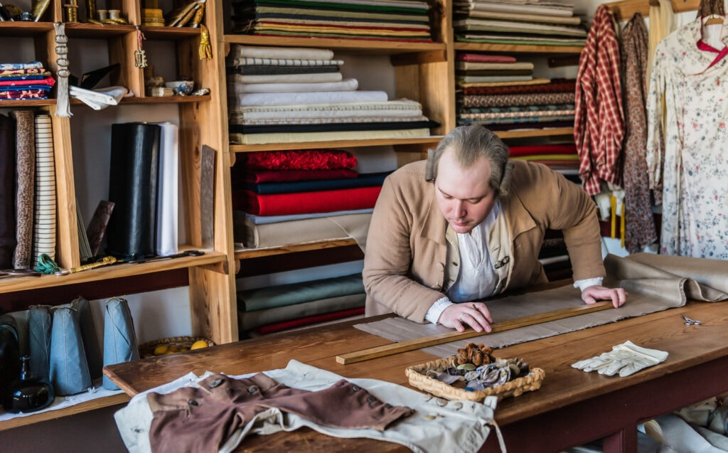 Tailor cuts cloth in Colonial Williamsburg Historical Site