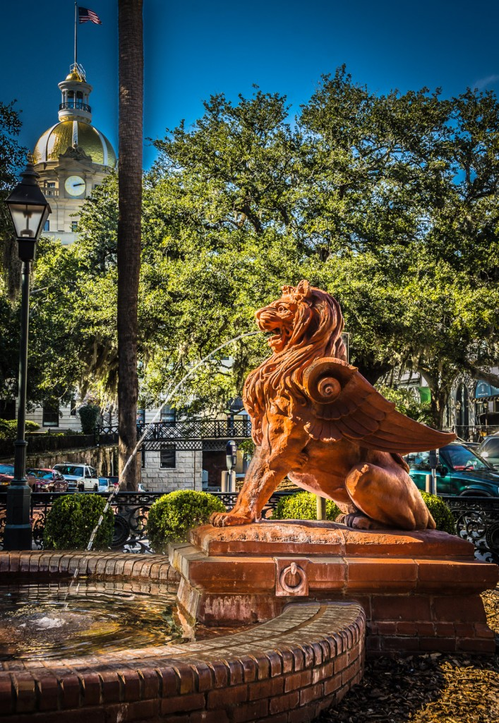 Savannah GA's spouting Lion Fountain in front of the Cotton Exchange, with gold roof of Savannah City Hall peeking out amidst trees in the background.