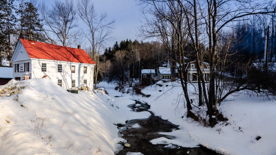 Frozen winter landscape in Grafton, Vermont includes Saxton River creek and the Old Fire Station.