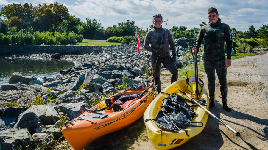 Lobster divers posing with spearguns and kayaks in Newport, RI.