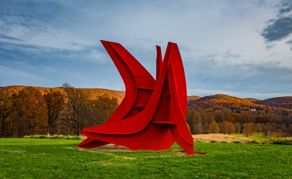 Alexander Calder's Five Swords cuts a crimson slash against the colorful backdrop of peak fall foliage in the Hudson Highlands .