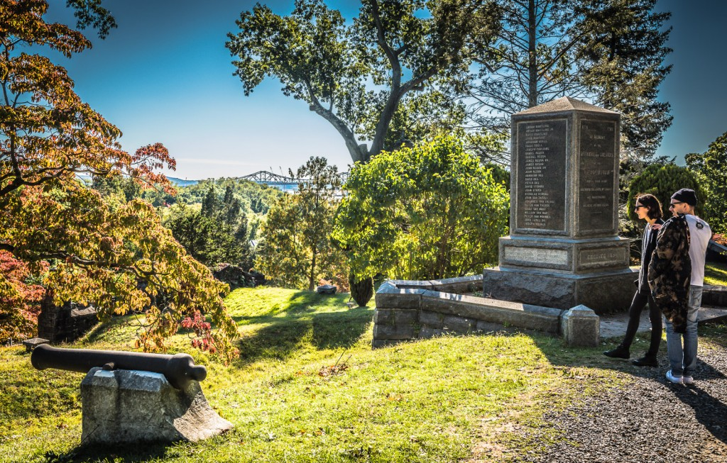 Couple on romantic getaway peer into landscape at Revolutionary War Monument - Sleepy Hollow Cemetery
