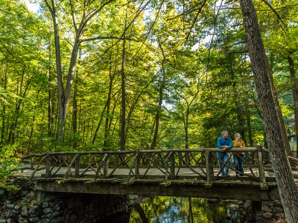Couple leans over Headless Horseman Bridge at Sleepy Hollow Cemetery