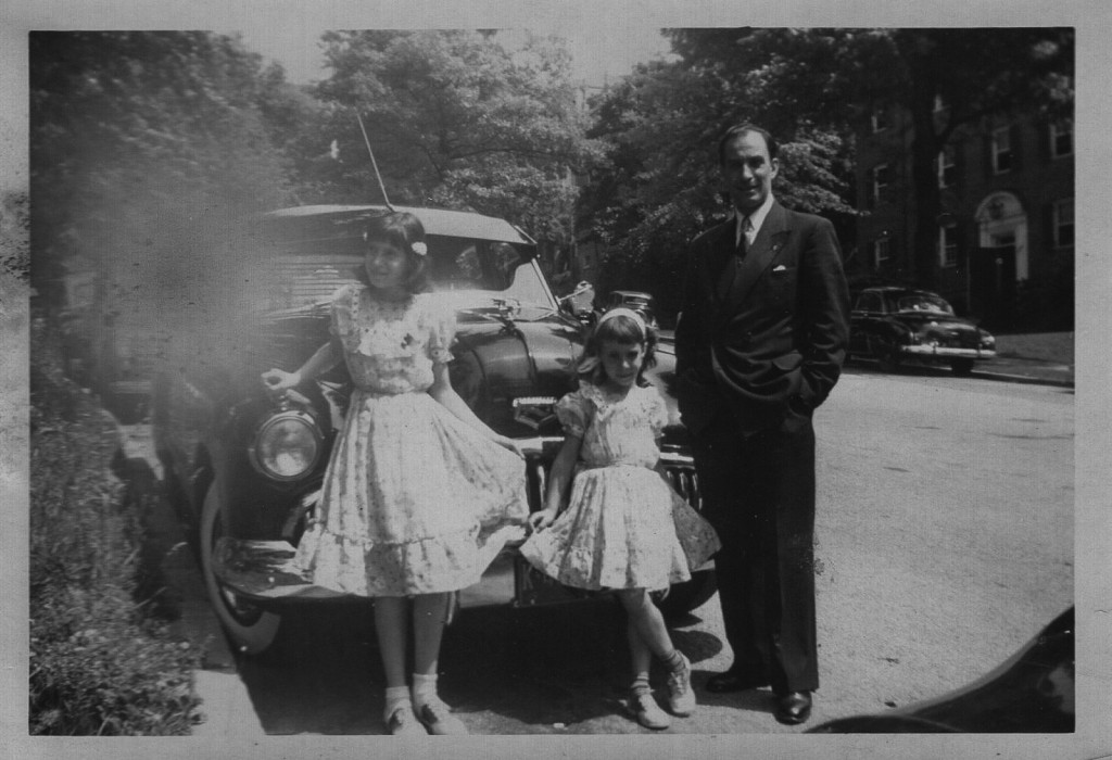 Two girls in frilly dresses with their father in front of a big, black Buick in the early 1950s.