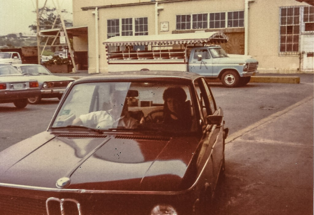 Sandra Foyt and her grandfather sitting in a Brown BMW.
