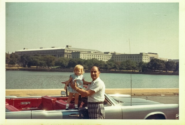 Grandfather holds up toddler Sandra Foyt on Lincoln Continental in Washington DC sometime in the early 1960s.