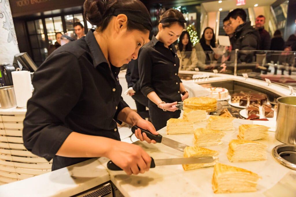 Women serve up Mille Crepe Cake at Plaza Hotel Food Hall.