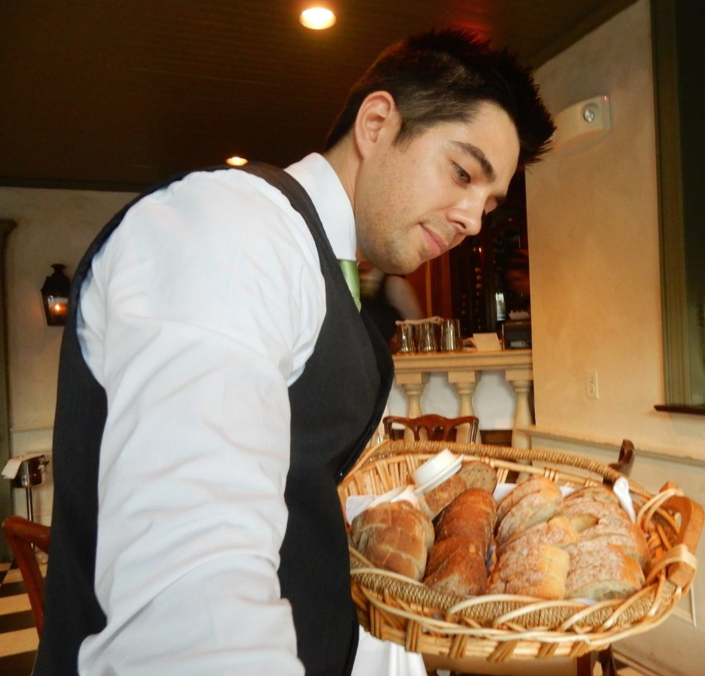 Waiter serves bread