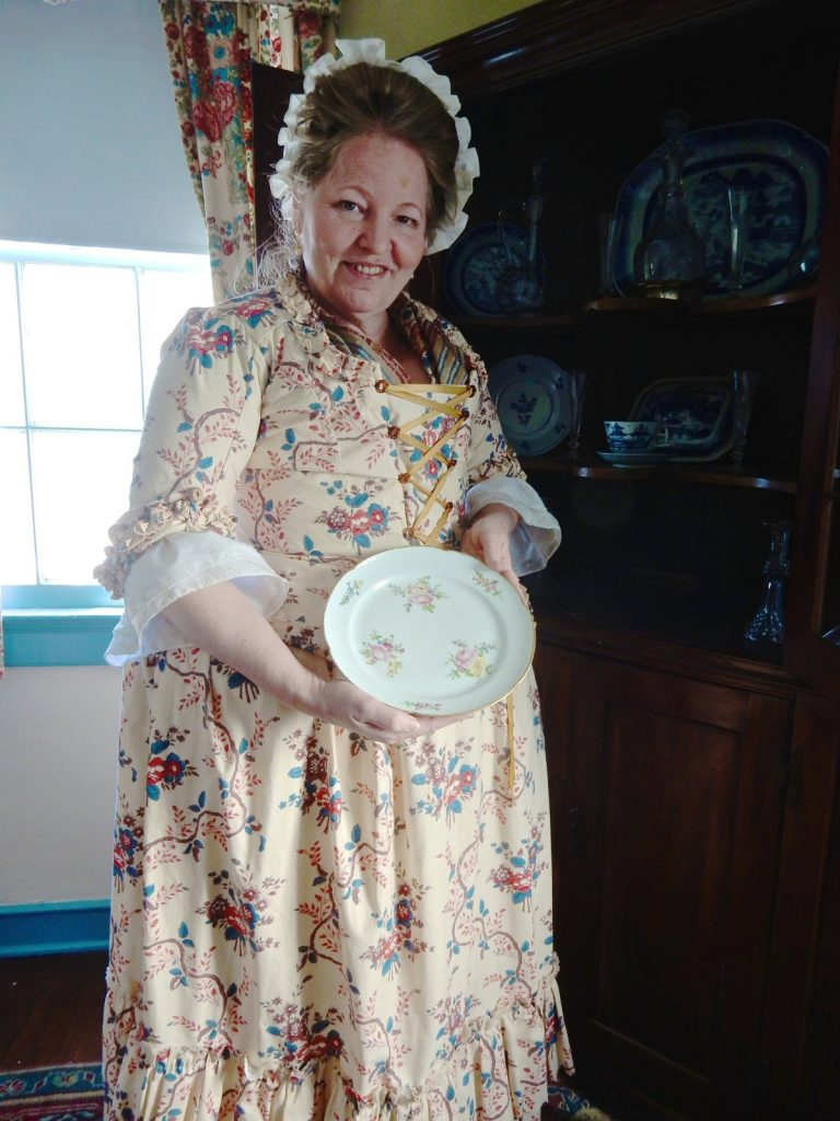 Docent Pat Sanftner holds up china plate at Schuyler Hamilton House in Morristown NJ
