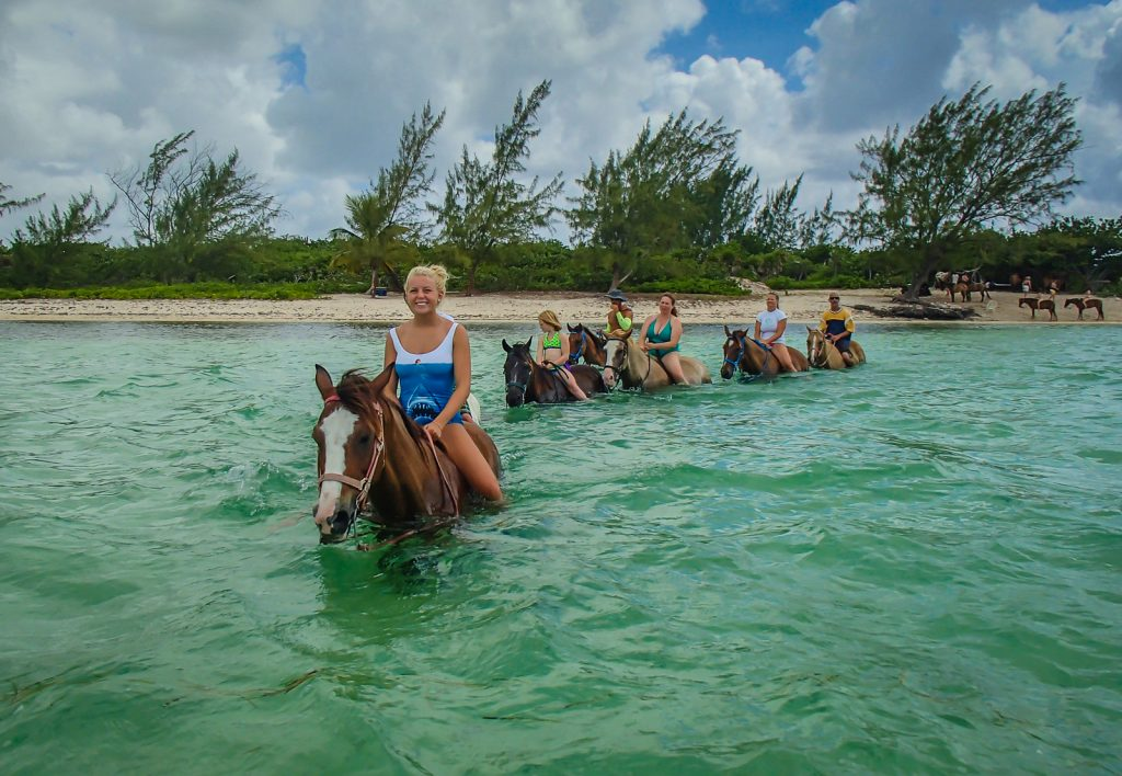 Girl riding horse with tour group in Grand Cayman