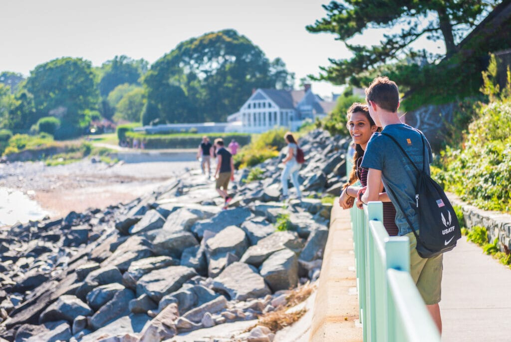 Young couple strolls along the Cliff Walk in Newport, Rhode Island.