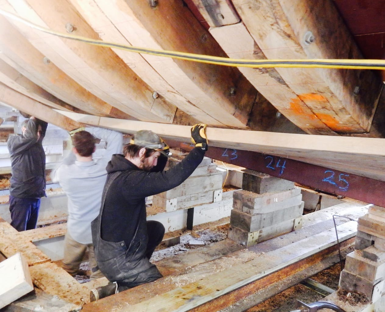 Affixing steamed, supple planks to hull of Mayflower II, Mystic Seaport CT