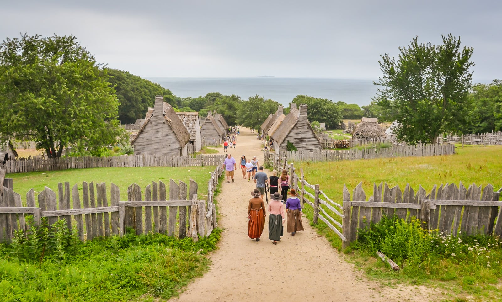 Costumed historic reenactors walk path at Plimoth Plantation.