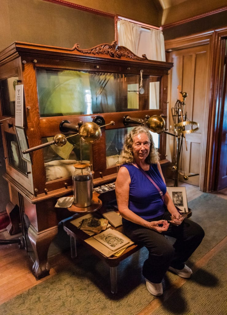 Woman posing with Electrostatic Machine at Dr Best House and Medical Exhibit in Middleburgh NY.