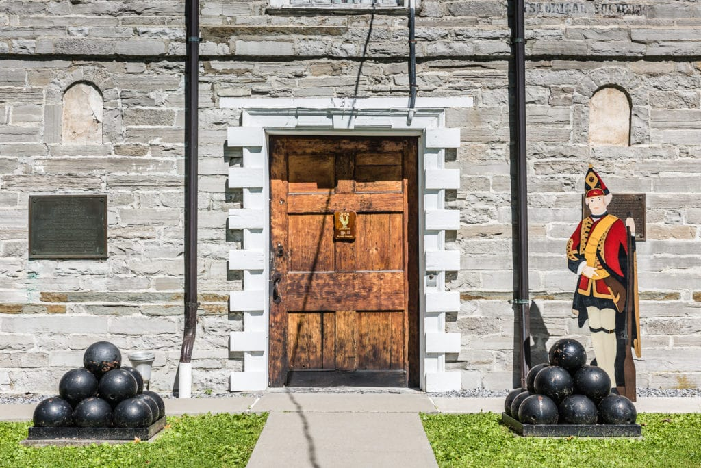 Front entrance of Old Stone Fort Museum in Schoharie, New York. A pile of cannon balls and wooden cutout soldier are posted at the door.