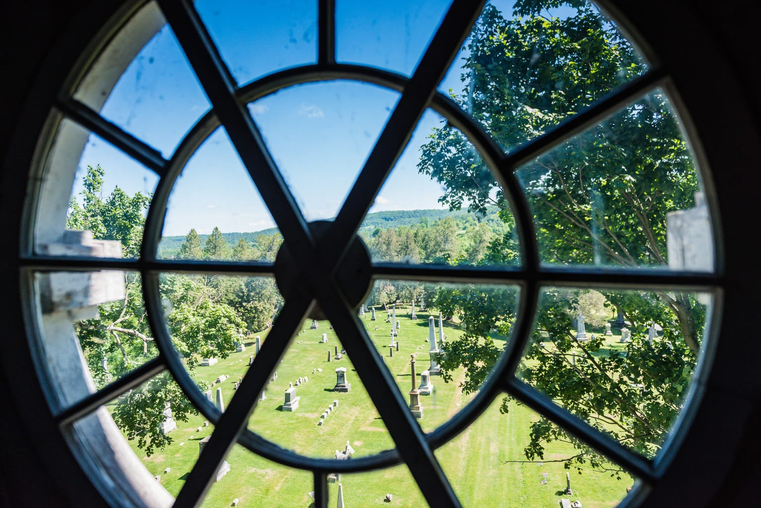 Round window looking out on cemetery on tower at the Old Stone Fort Museum in Schoharie NY.