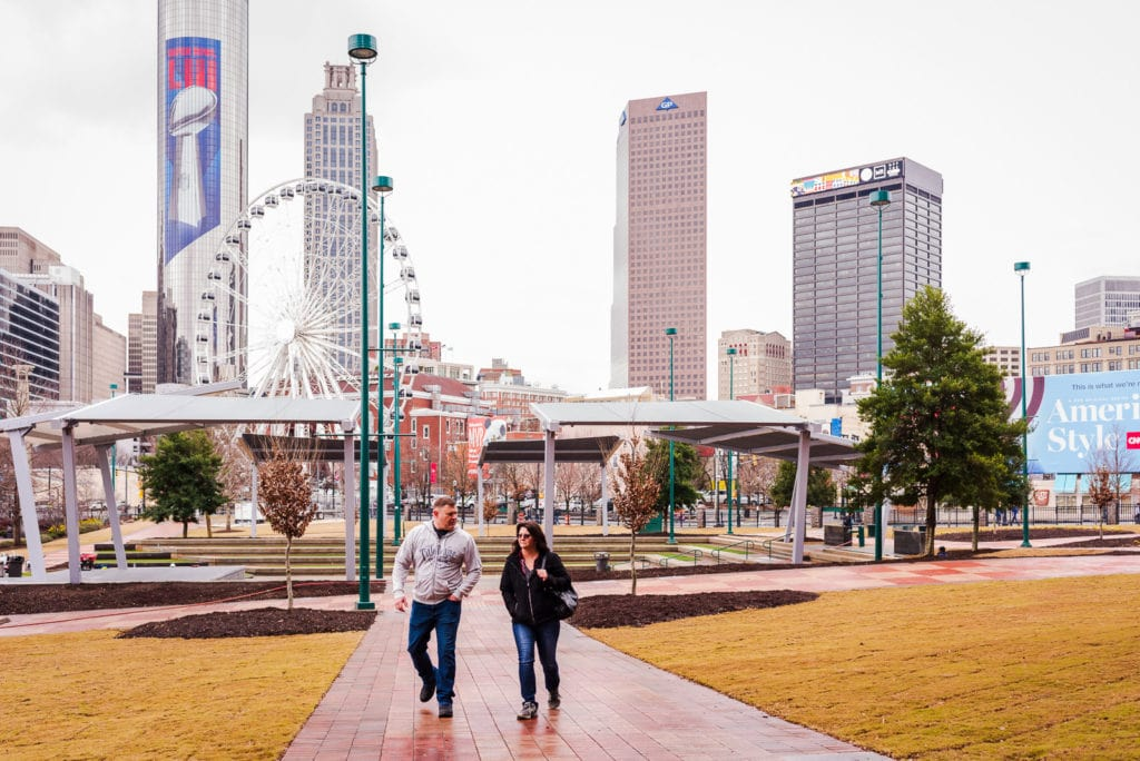 Couple walks in Centennial Olympic Park with city skyline in background.