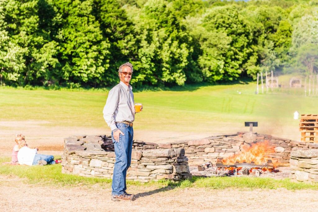 Patron enjoys summer night bonfire at Ommegang Brewery.