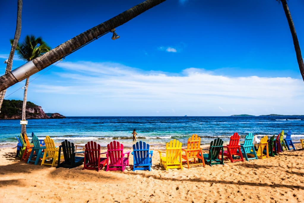 Colorful circle of Adirondack chairs on the beach at Iggies Beach Bar