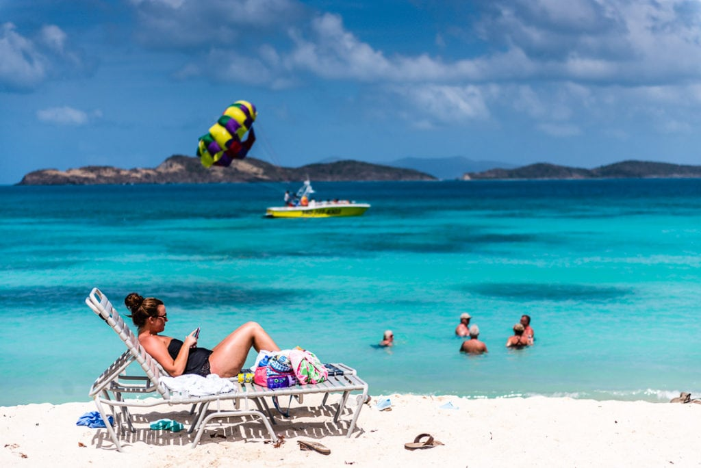 Tourist relaxes on chaise lounge at Saphire Bay.