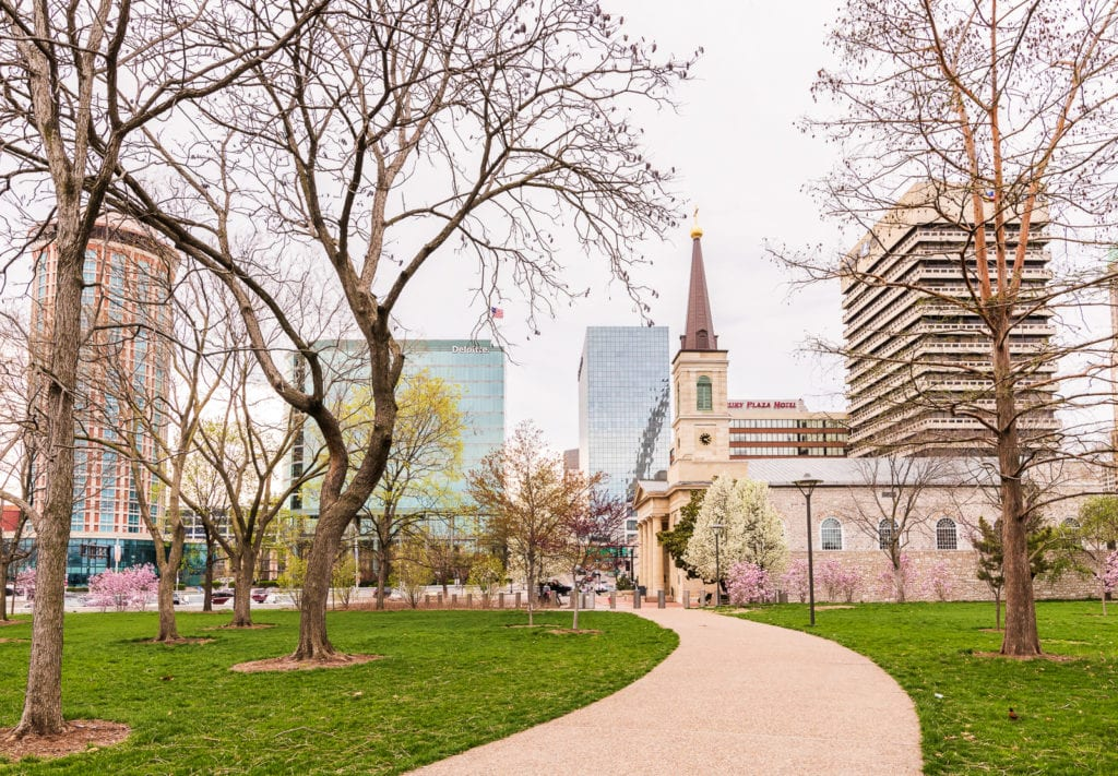 Curved walkway lined with trees covered in Spring blooms leading up to Old Cathedral with modern buildings of Downtown St Louis in background.